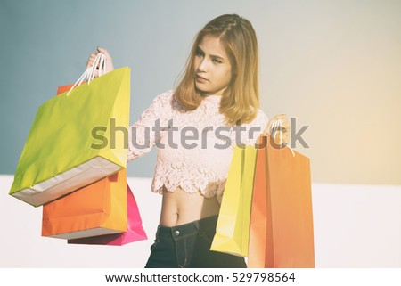 happiness, consumerism, sale and people concept - smiling young woman asian with shopping bags selective focus on bag ,vintage tone