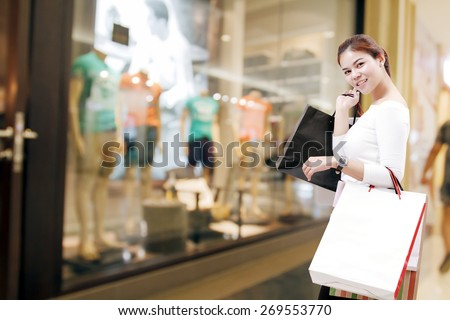 happiness, consumerism, sale and people concept - smiling young woman asian with shopping bags over mall/suppermarket background - stock photo