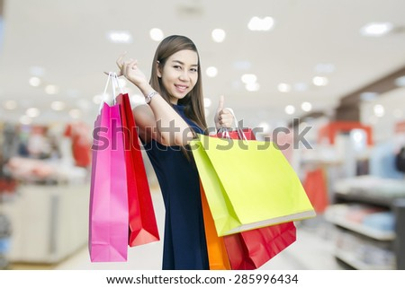 happiness, consumerism, sale and people concept - smiling young woman asian with shopping bags over mall/supermarket background - stock photo