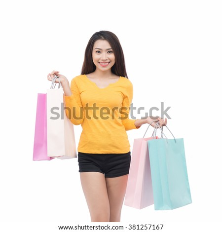 happiness, consumerism, sale and people concept - smiling young woman with shopping bags. beautiful young woman holding colored shopping bags isolated on white background