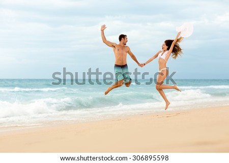 Happiness couple jumping on beach  - stock photo