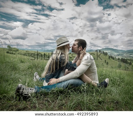 Happiness couple sitting on the green grass at sunny day time