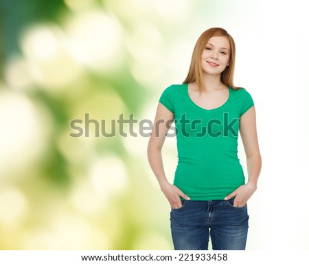 happiness, ecology, advertisement and people concept - smiling teenage girl in casual clothes over green background - stock photo
