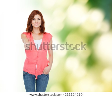 happiness, ecology, gesture and people concept - smiling teenage girl in casual clothes showing thumbs up over green background - stock photo