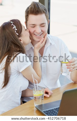 Happiness everywhere. Shot of a happy young man laughing while his loving girlfriend kissing him on a cheek during a date at the cafe - stock photo