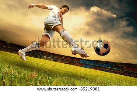 Happiness football player on field of stadium on sunrise sky - stock photo