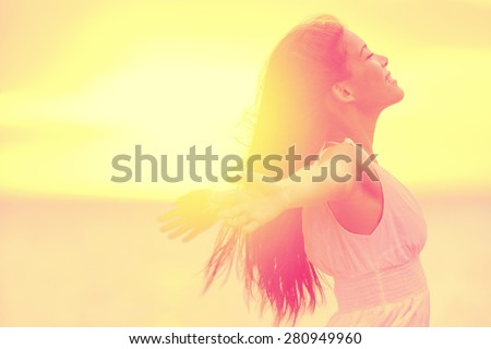 Happiness - Free happy woman enjoying sunset. Beautiful woman in white dress embracing the golden sunshine glow of sunset with arms outspread and face raised in sky enjoying peace, serenity in nature - stock photo