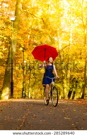 Happiness freedom and people concept. Redhaired beauty woman fashion girl on bicycle with red umbrella in autumnal park, having fun outdoor - stock photo