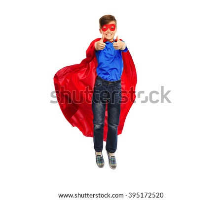 happiness, freedom, childhood, movement and people concept - boy in red super hero cape and mask flying in air and showing thumbs up - stock photo