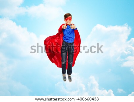 happiness, freedom, childhood, movement and people concept - boy in red super hero cape and mask flying in air and showing thumbs up over blue sky and clouds background