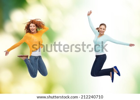 happiness, freedom, ecology, friendship and people concept - smiling young women jumping in air over green background - stock photo