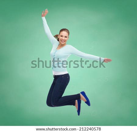 happiness, freedom, education and people concept - smiling young woman jumping in air over green board background - stock photo