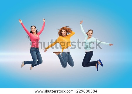 happiness, freedom, friendship, movement and people concept - smiling young women jumping in air over blue laser background - stock photo