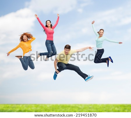 happiness, freedom, friendship, movement, summer and people concept - group of smiling teenagers in air over natural background - stock photo