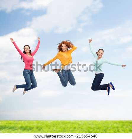 happiness, freedom, friendship, summer and people concept - group of smiling young women jumping in air over natural background - stock photo