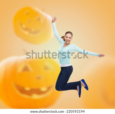 happiness, freedom, holidays and people concept - smiling young woman jumping in air over halloween pumpkins background - stock photo