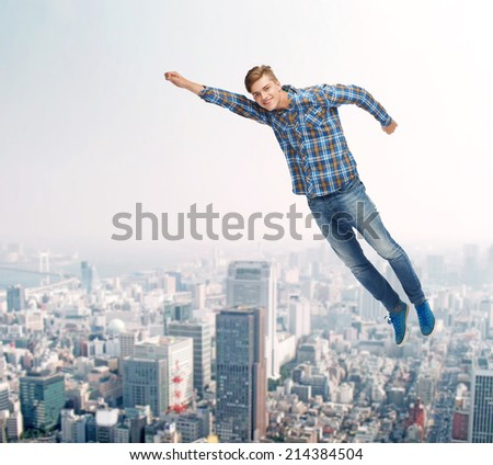 happiness, freedom, movement and people concept - smiling young man flying in air over city background - stock photo