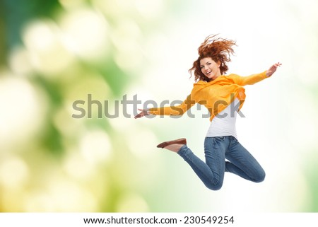 happiness, freedom, movement and people concept - smiling young woman jumping high in air over green background - stock photo