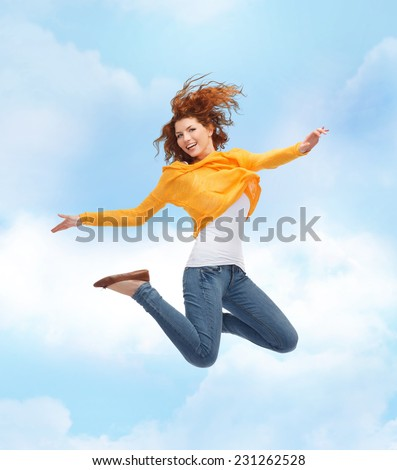 happiness, freedom, movement and people concept - smiling young woman jumping high in air over blue sky with cloud background - stock photo