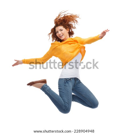 happiness, freedom, movement and people concept - smiling young woman jumping in air - stock photo