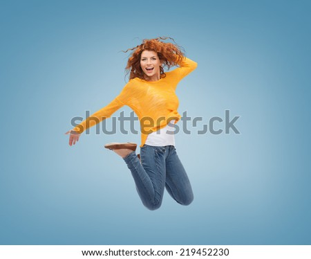 happiness, freedom, movement and people concept - smiling young woman jumping in air over blue background - stock photo