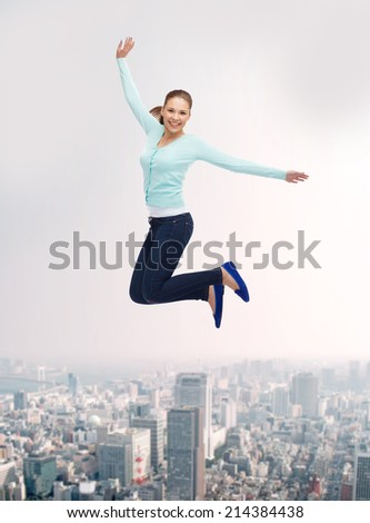 happiness, freedom, movement and people concept - smiling young woman jumping in air over city background - stock photo
