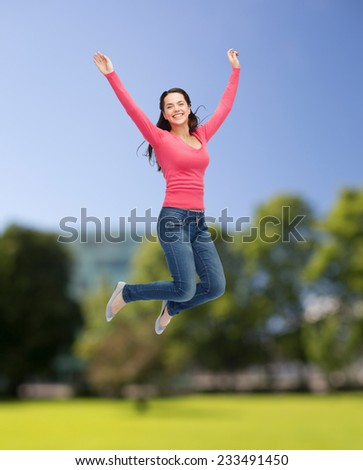 happiness, freedom, summer, nature and people concept - smiling young woman jumping in air over park background - stock photo