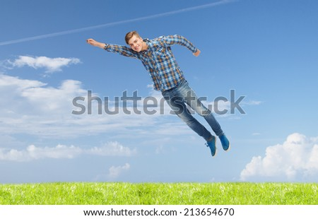 happiness, freedom, vacation, summer and people concept - smiling young man flying in air over natural background
