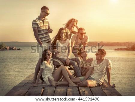 Happiness friends on pier under sunset light. - stock photo