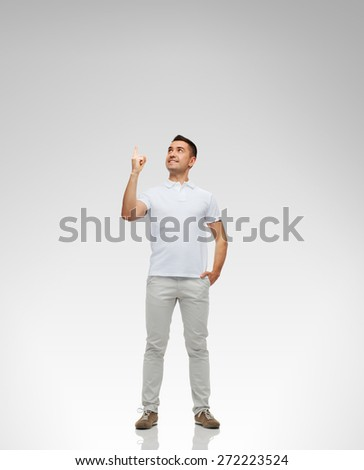 happiness, gesture and people concept - smiling man pointing finger up over gray background - stock photo