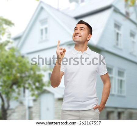 happiness, gesture and people concept - smiling man pointing finger up over house background