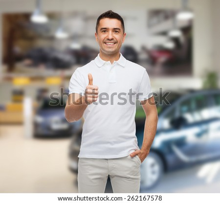 happiness, gesture and people concept - smiling man showing thumbs up over auto show background