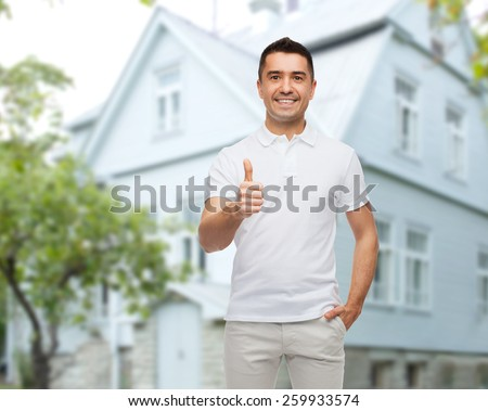 happiness, gesture and people concept - smiling man showing thumbs up over house background - stock photo