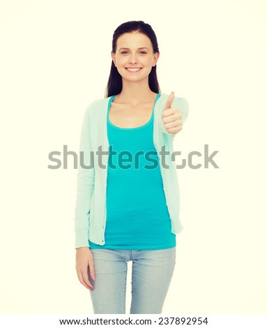 happiness, gesture and people concept - smiling teenage girl in casual clothes showing thumbs up - stock photo