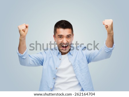 happiness, gesture, emotions, joy and people concept - happy laughing man with raised hands over gray background - stock photo