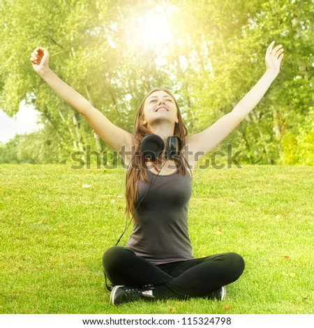 Happiness girl with headphones and raised arms enjoying nature in the park at sunny day. - stock photo