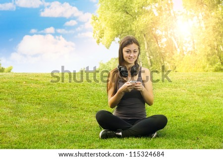 Happiness girl with headphones using mobile phone in the park. - stock photo