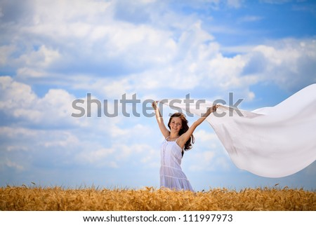 Happiness girl with white scarf on wind in wheat field