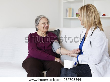Happiness grandmother sitting on the sofa with her female nurse in the living room . They are  looking at each other while female nurse measuring grandmother a blood pressure. - stock photo