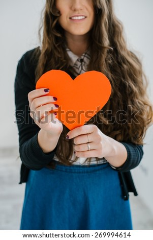 happiness, health, people, holidays and love concept - smiling young woman in white t-shirt holding red heart against the window - stock photo