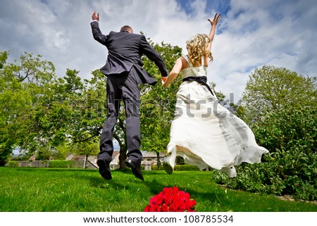 Happiness jump of bride and groom - stock photo