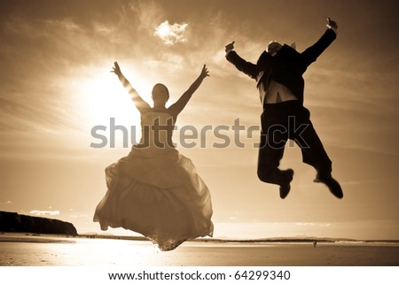 Happiness jump of bride and groom on the beach