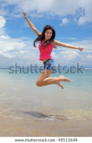Happiness! Jumping for joy on the beach - stock photo