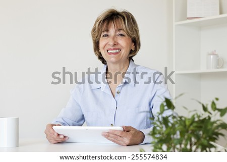 Happiness mature businesswoman sitting at desk holding a digital tablet and looking at camera. - stock photo