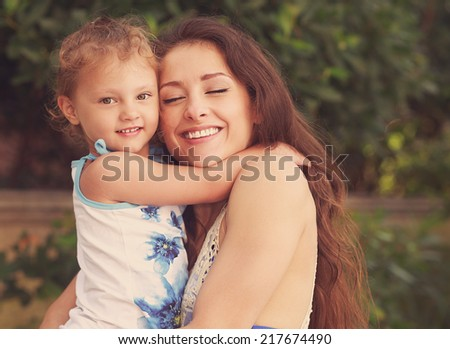 Happiness. Mother and kid girl cuddling outdoors summer background. Instagram effect portrait - stock photo