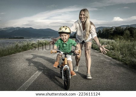 Happiness Mother and son on the bicycle outdoor - stock photo