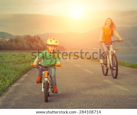 Happiness Mother and son on the bicycles funning outdoor - stock photo