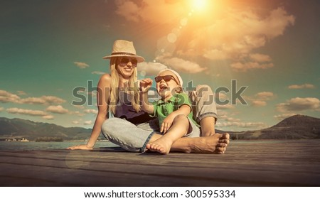 Happiness mother and son on the pier at sunny day under sunlight. - stock photo