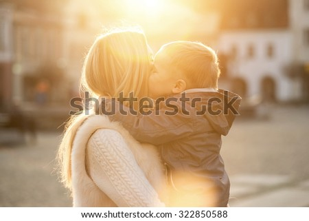 Happiness mother and son on the street at sunny day. - stock photo