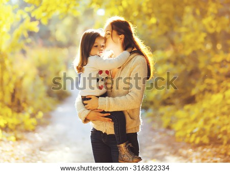 Happiness mother! Mom kissing child in sunny autumn park  - stock photo